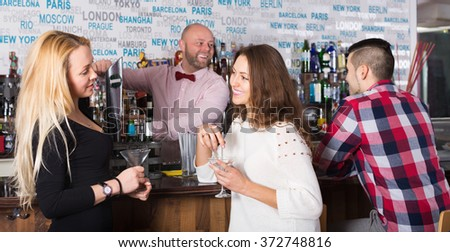 Cheerful young friends drinking and chatting with happy barman at bar counter - stock photo