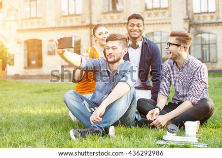 Cheerful young friends photographing themselves near university - stock photo