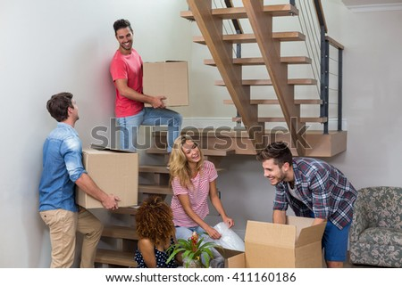 Cheerful young friends relocating in new house - stock photo