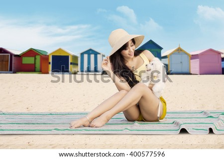 Cheerful young girl and her dog sitting on the mat at the beach with the beach huts background - stock photo
