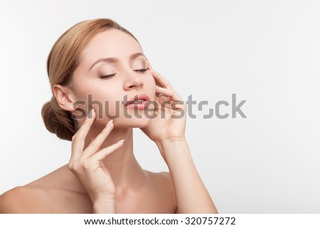 Cheerful young girl is caring of her skin. She is standing and touching her face with pleasure. She closed her eyes with pretty smile. Isolated and copy space in right side - stock photo