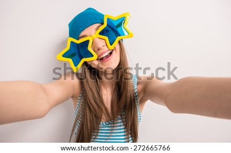 Cheerful young girl is posing on gray background in glasses in the shape of stars. - stock photo