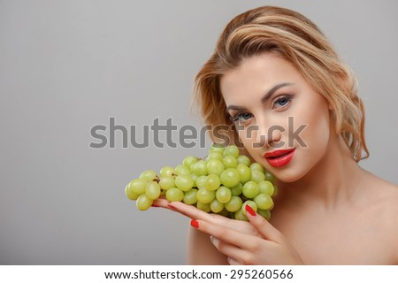 Cheerful young girl is touching bunch of grapes to her face gently. She is looking at the camera with desire. Her eyes and fingernails are red. Isolated on grey background and copy space in left side - stock photo