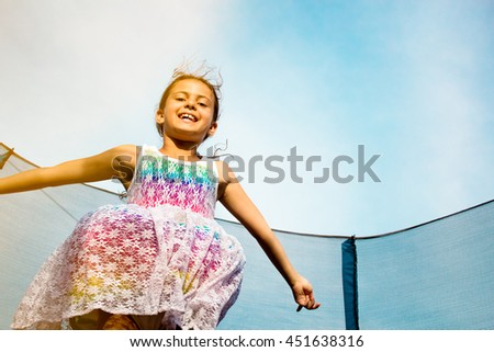 cheerful young girl jumping on trampoline