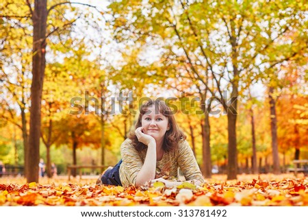 Cheerful young girl lying on the ground in fallen leaves on a bright autumn day