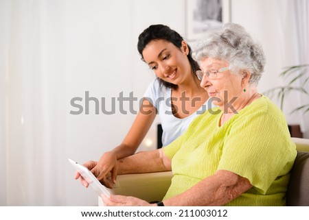 cheerful young girl with an elderly woman playing together with digital tablet at home - stock photo