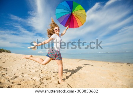 Cheerful young girl with rainbow umbrella having fun on sunny day on the beach with beautiful ocean and blue sky on background.Travel, holidays, vacation, healthy lifestyle concept