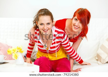 Cheerful young girlfriends sitting on sofa and have fun - stock photo