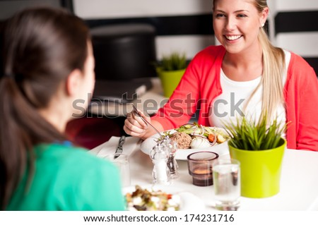 Cheerful young girls having dinner at a restaurant - stock photo