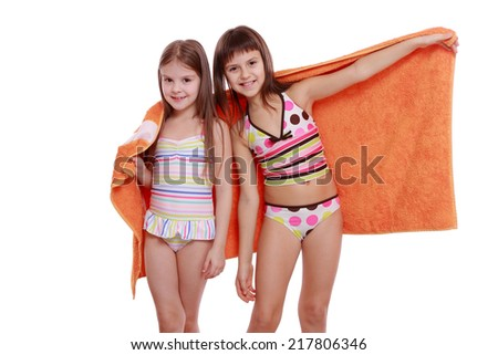 cheerful young girls holding orange towel isolated over white background - stock photo