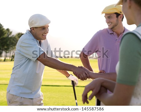 Cheerful young golfers shaking hands on golf course - stock photo
