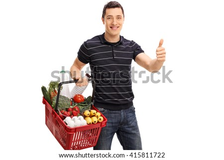 Cheerful young guy carrying groceries and giving a thumb up isolated on white background - stock photo