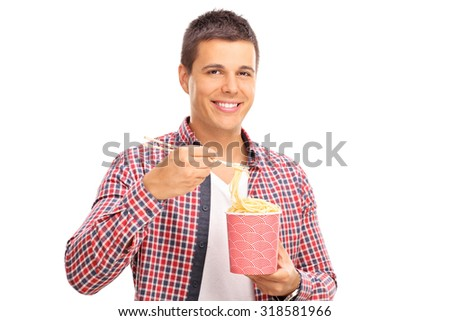 Cheerful young guy eating Chinese food with sticks from a paper box isolated on white background