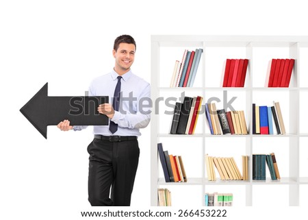 Cheerful young guy holding a big black arrow pointing right and leaning on a white bookshelf isolated on white background - stock photo