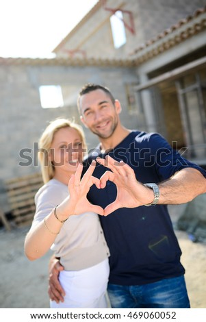 cheerful young happy couple in love making heart shape with their hands in front of construction site of their new house