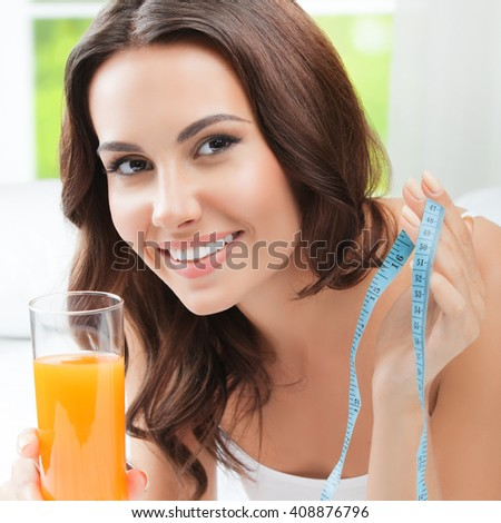 Cheerful young happy smiling beautiful woman with orange juice and measure tape, indoors - stock photo