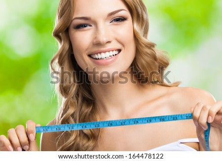Cheerful young happy smiling blond woman with measure tape, outdoors - stock photo