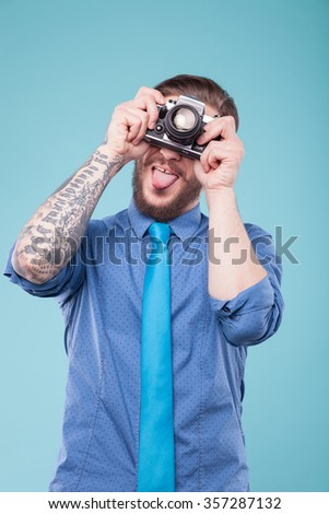 Cheerful young hipster is making fun with camera. He is photographing and showing his tongue. The man is standing with joy. Isolated on blue background