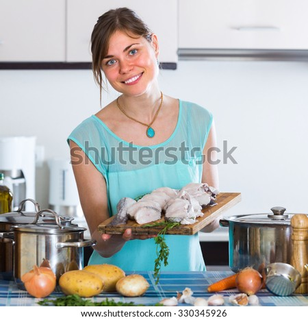 Cheerful young housewife  cooking sliced fish at home kitchen - stock photo