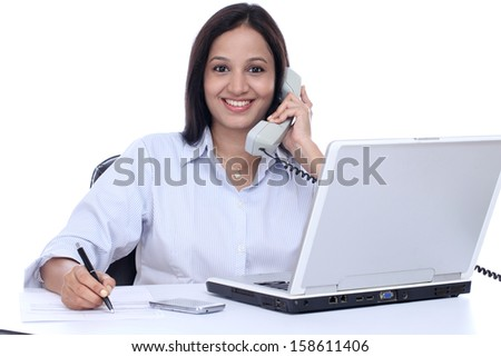 Cheerful young Indian business woman talking on phone