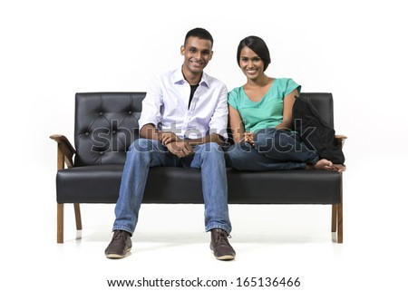 Cheerful young Indian couple sitting on a retro sofa. Isolated on white background. - stock photo