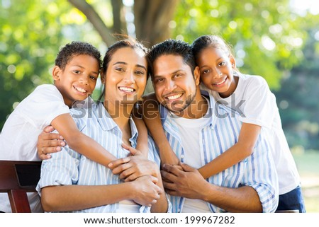 cheerful young indian family sitting together in the park - stock photo