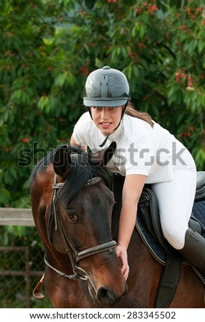 Cheerful young jockey woman ridding  with purebred horse outdoors - stock photo