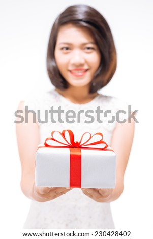 Cheerful young lady giving a present - stock photo