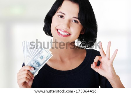Cheerful young lady holding cash - dollars USD