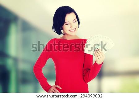Cheerful young lady holding cash - polish zloty (pln) - stock photo