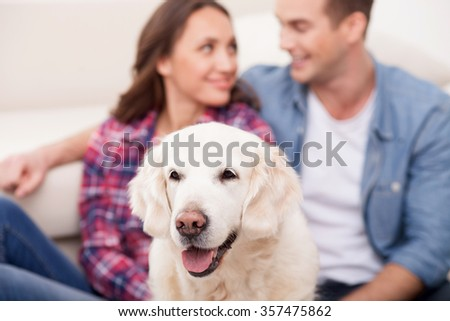 Cheerful young loving couple is resting at home. They are sitting on flooring near their dog. The man and woman are embracing and smiling. Focus on the animal - stock photo