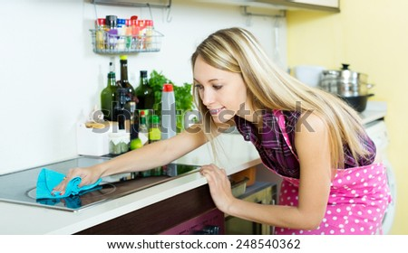Cheerful young maid cleans modern stove cleaner at his home - stock photo