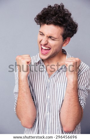 Cheerful young man celebrating his success over gray background - stock photo