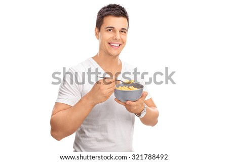 Cheerful young man eating cereal from a bowl and looking at the camera isolated on white background - stock photo