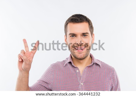Cheerful young man gesturing with two fingers