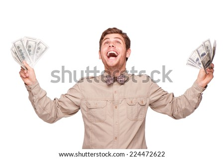 Cheerful young man holding soft money and happily smiling, isolated on white - stock photo