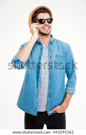 Cheerful young man in hat and sunglasses standing and talking on mobile phone over white background - stock photo