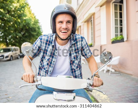 Cheerful young man in helmet is riding on scooter in town. - stock photo