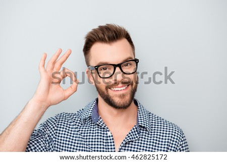 "Cheerful young man in spectacles showing ""OK"" gesture"