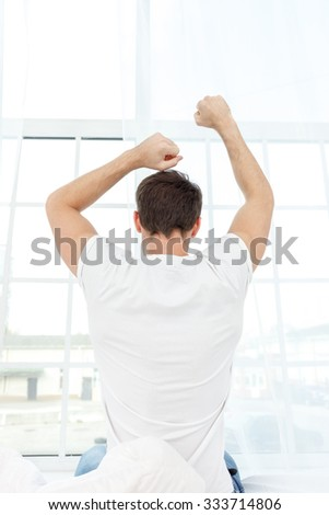 Cheerful young man is stretching his arms after waking up. He is sitting on bed and relaxing. Focus on his bed - stock photo