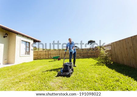 cheerful young man mowing lawn at home - stock photo