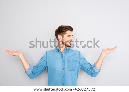 Cheerful young man presenting products in both hands - stock photo