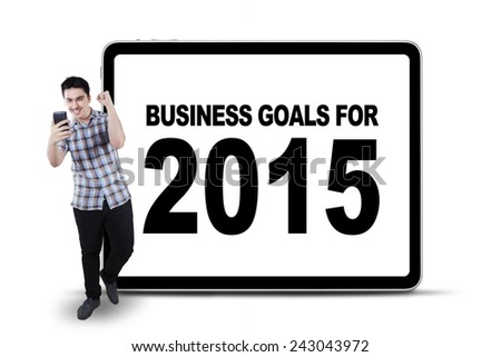 Cheerful young man reading good news on cellphone in front of a text of business goals for 2015 on board - stock photo