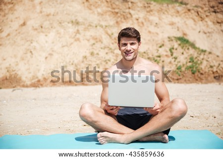 Cheerful young man relaxing and using laptop on the beach - stock photo