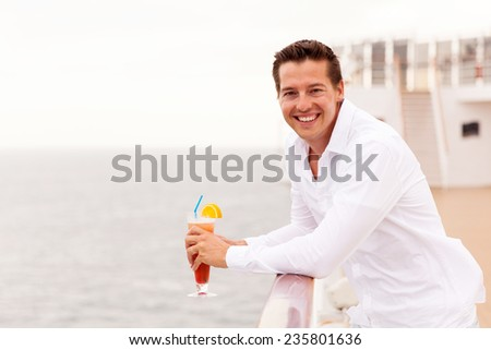 cheerful young man relaxing on cruise deck with cocktail - stock photo