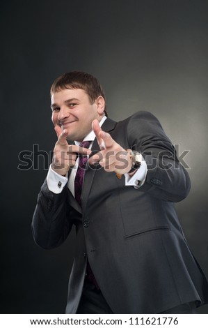 Cheerful young man shows in the frame with your fingers. Choice. On a dark background. - stock photo