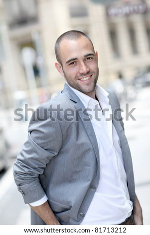 Cheerful young man walking in town - stock photo
