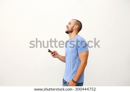 Cheerful young man walking with mobile phone against white background  - stock photo