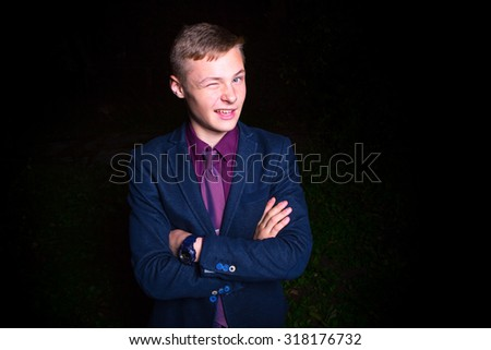 Cheerful young man winking over black background - stock photo