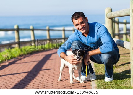 cheerful young man with his pet dog at the beach - stock photo
